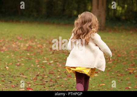 Little girl running across leaves in a park - Stock Image