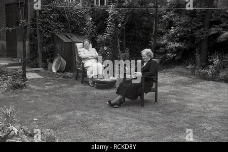 1950s, historical, daughter and her mother elderly lady sitting in chairs in a back garden, with the eldery lady reading a book, England, UK. - Stock Image