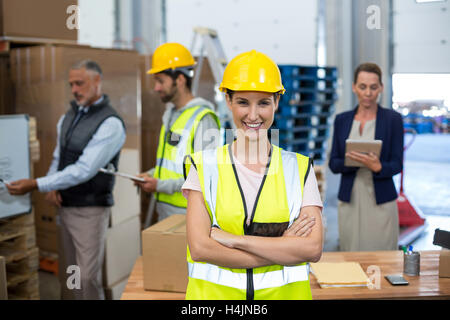 Portrait of female warehouse worker standing with arms crossed - Stock Image