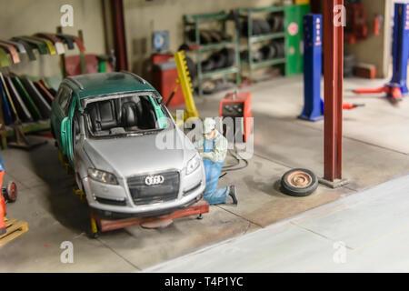 Miniature model of a mechanic welding an Audi car, at Kolejkowo, Wrocław, Wroclaw, Wroklaw, Poland - Stock Image