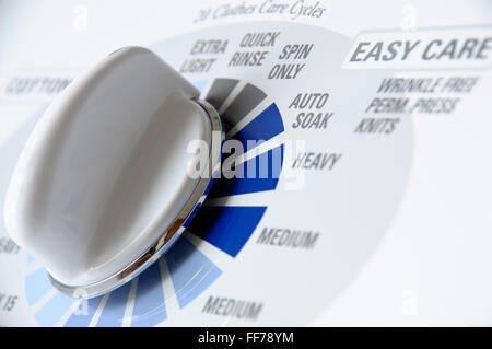 Washing machine dial closeup photo with wash cycle settings - Stock Image