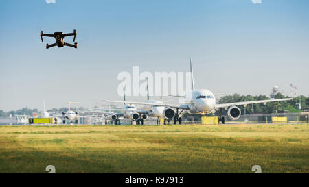 Unmanned drone flying near row of commercial airplanes at airport, flight disruption concept - digital composite - Stock Image