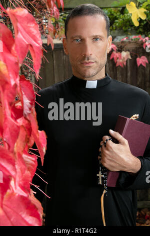 Portrait of handsome priest holding his bible and looking at camera while standing in garden - Stock Image