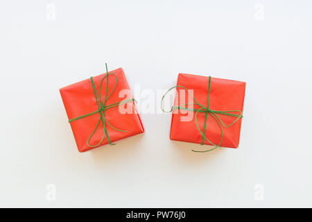 Two gift boxes wrapped in red paper tied with green ribbon. White background. Holiday New Years Christmas corporate presents shopping sale. Poster ban - Stock Image
