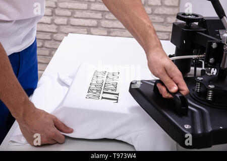 Man printing on t shirt in workshop - Stock Image