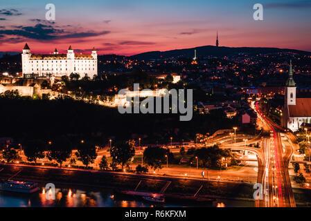 Evening panorama of Bratislava city just after sunset with beautiful pink sky and night illumination. Long exposure photo. - Stock Image