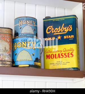 Tea, Honey and Molasses on a General Store shelf: Early 20th century cans of tea, honey and molasses decorate this museum display. - Stock Image
