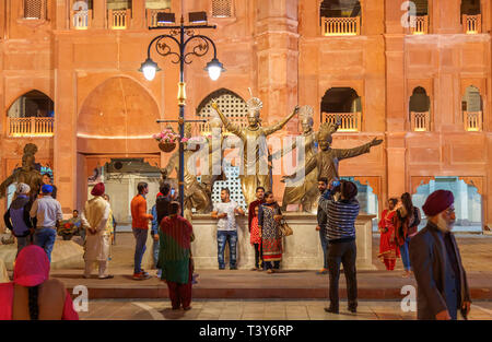 Local people enjoying themselves in Amritsar town centre at night posing and taking pictures and selfies next to large roadside statues - Stock Image