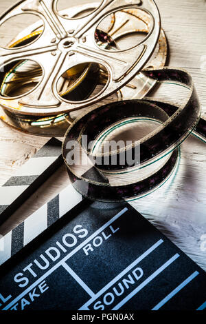 Vintage film claper with film reel placed on wood. Filmammakers equipment background - Stock Image