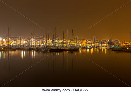 Sea port by night full of lights of sailboats, yachts and small boats that rest in the port. Sometimes as in this - Stock Image