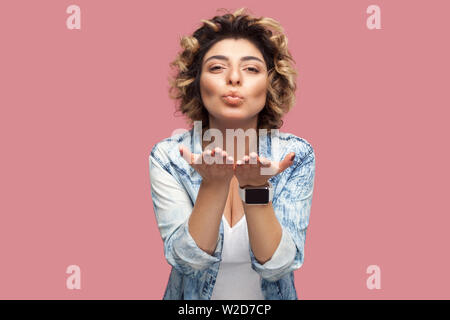 Portrait of happy in love young woman with curly hairstyle in casual blue shirt standing, looking at camera and sending air kiss with happiness. indoo - Stock Image