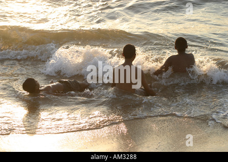 Children playing in the surf Negumbo beach Sri lanka - Stock Image