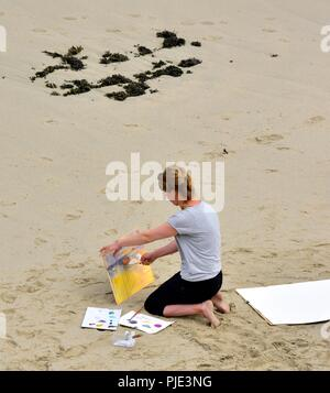 A woman painting on a beach,Sennen Cove, Cornwall,England,UK - Stock Image