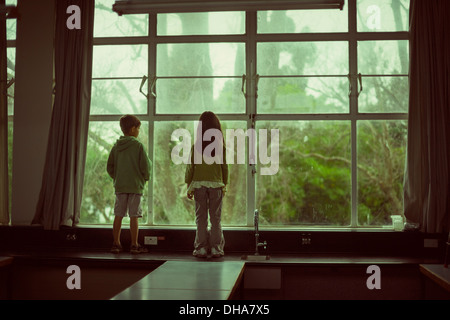 Children stand on bench and look out of large second floor window at trees. - Stock Image