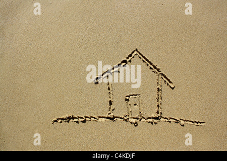 Drawing of a house on wet sand. Please see my collection for more similar photos. - Stock Image