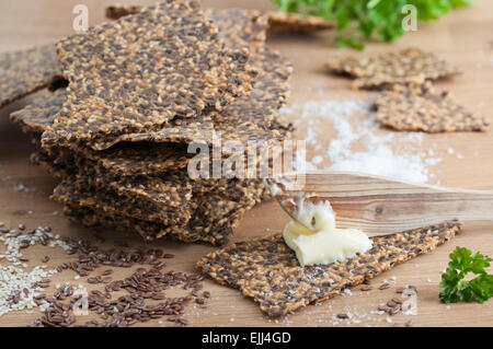 Homemade gluten free flax seed and sesame seed crispbread with butter and sea salt. All organic. - Stock Image