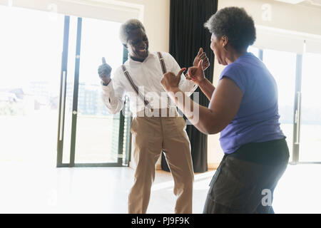 Playful, active senior couple dancing - Stock Image
