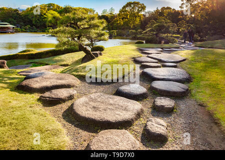 9 April 2019: Tokyo, Japan - Kiyosumi Garden, stepping stones beside the lake. Flare as sun sets on top right. - Stock Image
