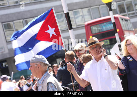 London, UK - 30 June 2018: A demonstrator holding a Cuban flag joined the thousands of people taking part in a national demonstration and celebration to mark the 70th anniversary of the NHS on 30 June. The demonstration organised by  The People's Assembly amongst other seek for A publicly owned NHS that is free for all and proper funding and proper staffing.  Credit:  David Mbiyu / Alamy Live News - Stock Image