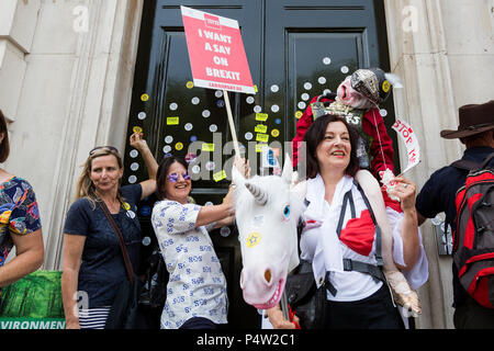London, UK. 23 June 2018.Anti-Brexit march and rally for a People's Vote in Central London. Protesters putting anti-brexit stickers on the front door of the Cabinet Office. - Stock Image