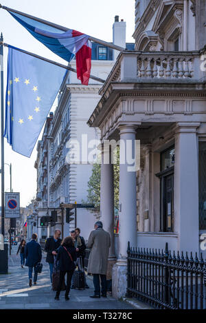 People wait outside the entrance to the French Consulate building Cromwell Road, London. French Tricolour and EU flags hang above entrance porch. - Stock Image