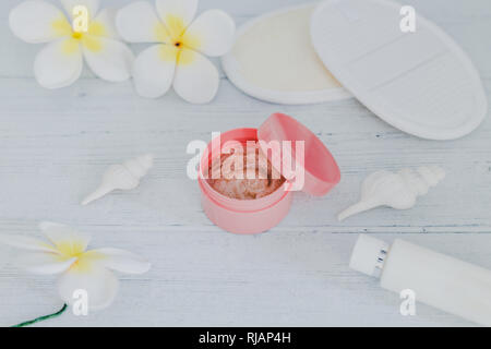 spa inspired set of scrub body lotions surrounded by flowers and seashells on light colored wood, concept of luxury and natural products - Stock Image