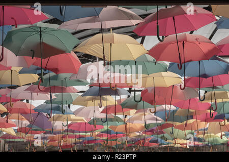 Faded color hanging umbrella display  viewed across . More subdued version than typical - Stock Image