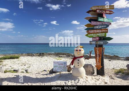 Signpost with directions to World travel destinations and Christmas Snowman on Sandy Beach of Punta Sur Ecological Reserve in Cozumel, Mexico - Stock Image