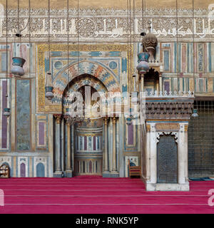 Colorful decorated marble wall with engraved Mihrab (niche) and wooden Minbar (Platform) at the Mosque and Madrassa (School) of Sultan Hassan, Cairo,  - Stock Image