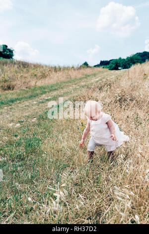 Girl walking on meadow - Stock Image