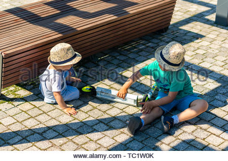 Two boys playing on the ground next to a wooden - Stock Image