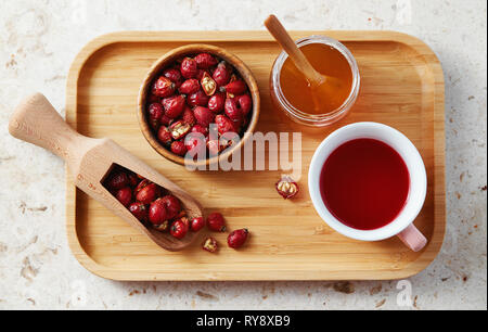 Top view of delicious rose hip tea in cup with dried rose hips on wooden tray. - Stock Image