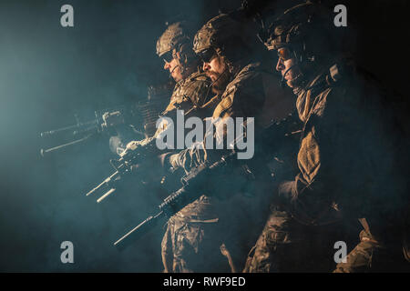 Group of security forces in combat uniforms with rifles, lined in the face of danger. - Stock Image