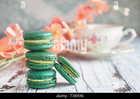 Stack of fresh french green tea macarons on a white rustic table with flowers and antique tea cup blurred in background.. - Stock Image