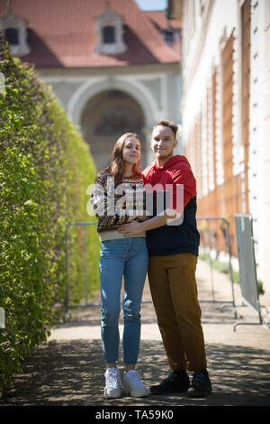 A young couple traveling. A couple in bright clothes standing on the street and hugging. Mid shot - Stock Image