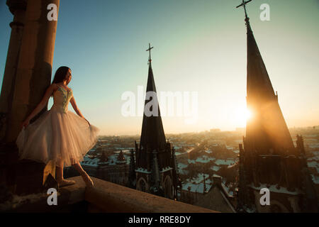 Beautiful ballerina dances on the balcony against the background of cityscape and church towers at sunset. - Stock Image
