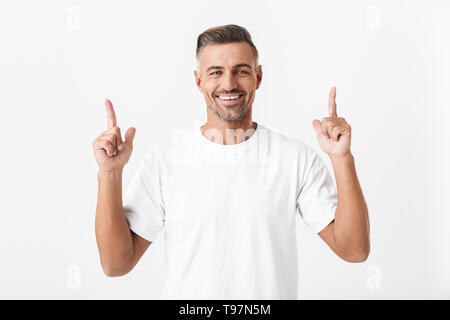 Image of unshaved man 30s with bristle wearing casual t-shirt pointing fingers upward at copyspace isolated over white background - Stock Image