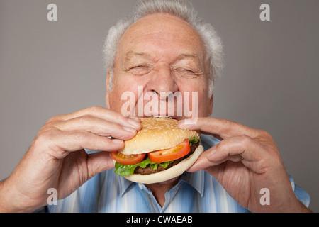 Senior man eating burger - Stock Image