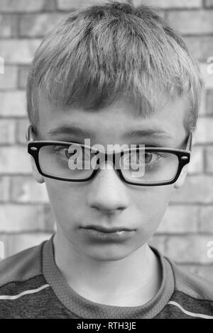 Black and white portrait of upset preteen boy wearing glasses - Stock Image