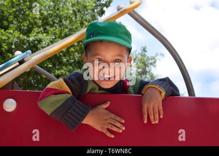portrait happy little boy in playground - Stock Image