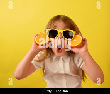 A girl is holding a juicy fruit orange on an isolated yellow background. The child is wearing glasses with a funny - Stock Image