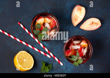 cold tea peach with ice in glasses on a blue background. view from above - Stock Image