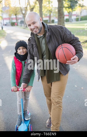 Portrait happy father and son playing in autumn park - Stock Image