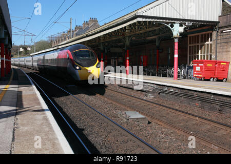 A Virgin train passes through Oxenholme station in the Lake District,  Cumbria, northern England - Stock Image