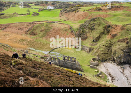 Walkers hiking up on the steep coastal footpath from the old Porcelein works at Porth Llanlleiana. Cemaes, Isle of Anglesey, Wales, UK, Britain, Europ - Stock Image