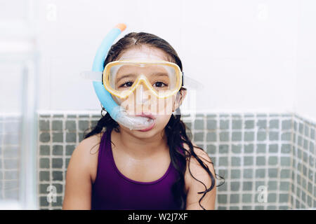 portrait of a happy pretty little girl with snorkel goggles in the tub while taking a bath in the bathtub, kids hygiene concept, copy space for text - Stock Image
