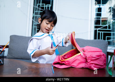 happy toddler with school uniform preparing her self and put some stationary in her backpack - Stock Image