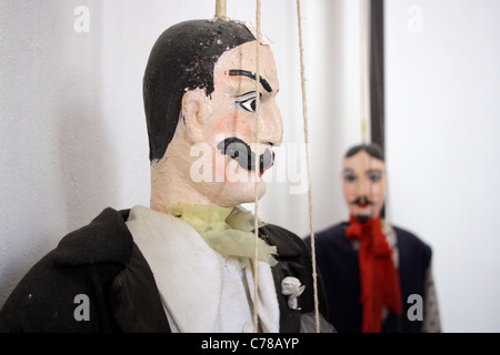 Close of of a large male Sicilian marionette / puppet with mustache in focus. Puppet in the background out of focus - Stock Image
