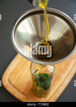 Vegetable oil being poured into a bottle with chopped wild garlic. - Stock Image