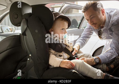 Father fastening son's (18-23 months) seat belt - Stock Image